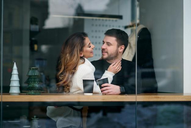 Ragazza carina con il suo ragazzo seduto all'interno di un caffè e bere caffè profumato caldo mentre fuori fa freddo. amore e romanticismo