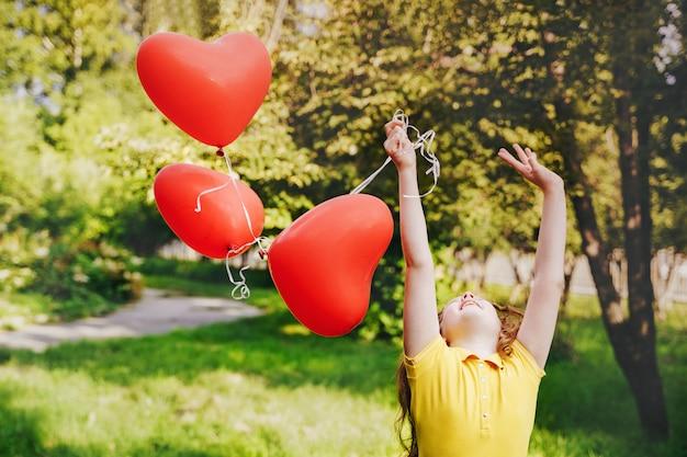 Ragazza carina con palloncini rossi all'aperto.