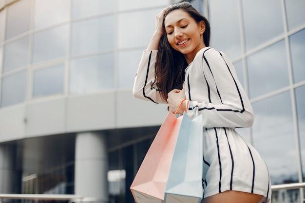 Ragazza carina con shopping bag in una città