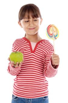 Ragazza carina con una lecca-lecca e una mela su sfondo bianco