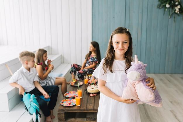 Ragazza carina con unicorno giocattolo sulla festa di compleanno