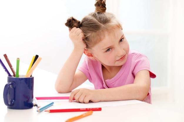 Ragazza carina di disegno con matite colorate