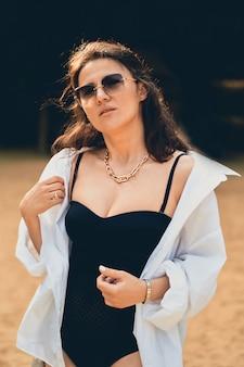 Ragazza carina di moda sulla spiaggia in costume da bagno nero, camicia bianca e occhiali.