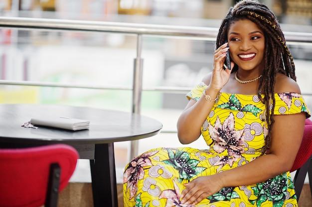 Ragazza carina di piccola altezza afro-americana con i dreadlocks, indossare in abito giallo colorato, seduto sul caffè al centro commerciale e parlando al telefono.