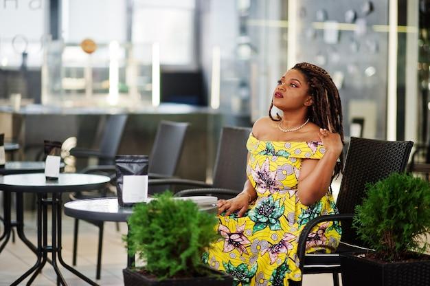 Ragazza carina di piccola altezza afroamericana con i dreadlocks, indossata in abito giallo colorato, seduta sulla caffetteria al centro commerciale.