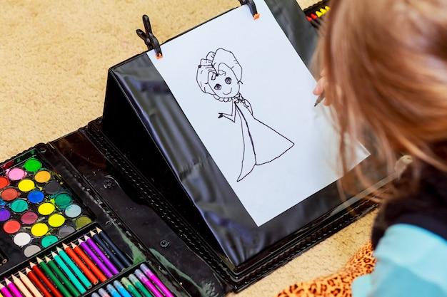 Ragazza carina disegno con matite colorate