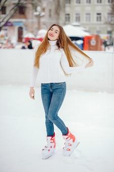 Ragazza carina e bella in un maglione bianco in una città d'inverno