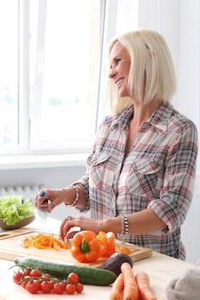 Ragazza carina e bionda in cucina