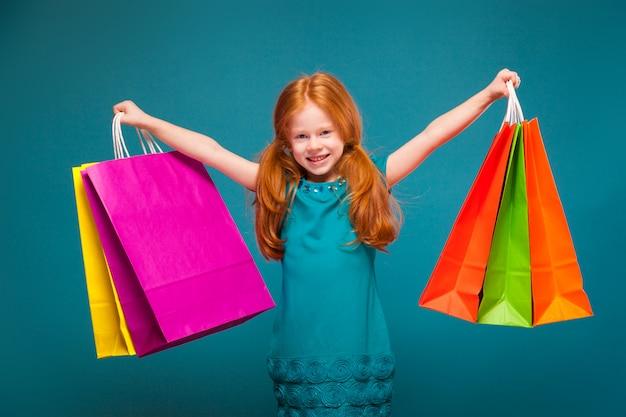 Ragazza carina e carina in abiti blu con lunghi capelli rossi si prende cura di diversi pacchetti