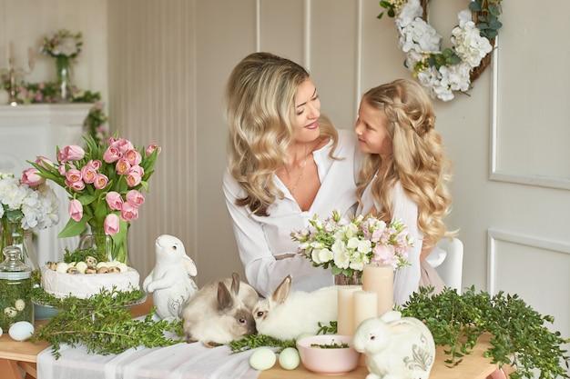 Ragazza carina e madre che giocano con i conigli