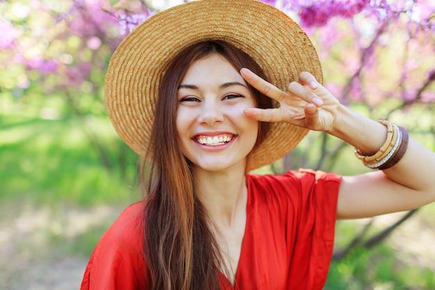 Ragazza carina giocosa che fa una faccia buffa e che mostra segni, in posa nel parco di primavera su alberi in fiore