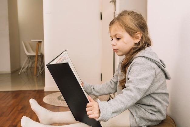 Ragazza carina godendo la lettura sul pouf