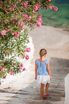 Ragazza carina in abiti blu divertirsi all'aperto per le strade di mykonos