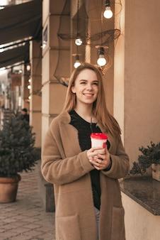 Ragazza carina in abiti primaverili, indossa un cappotto, in piedi in strada con una tazza di caffè in mano, guardando in alto e sorridente sullo sfondo di un muro beige