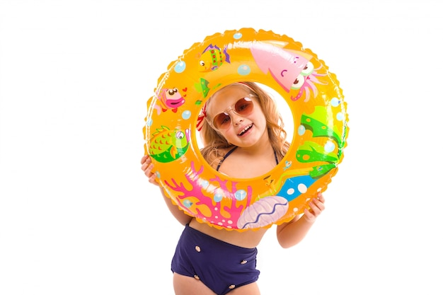 Ragazza carina in bikini a strisce rosse, pantaloni blu, occhiali da sole e corona rosa stanno con l'anello di gomma in mano