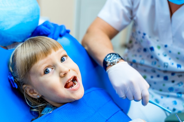 Ragazza carina in clinica dentale. bambino in gabinetto stomatologico a bocca aperta.