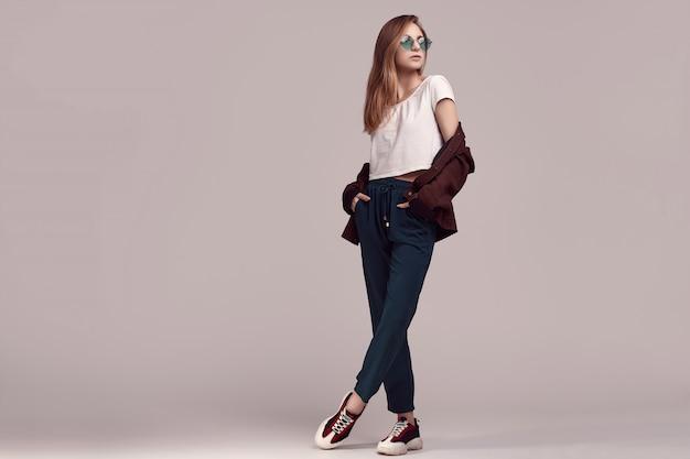 Ragazza carina in giacca di moda e occhiali di colore