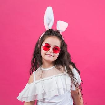 Ragazza carina in orecchie da coniglio e occhiali da sole