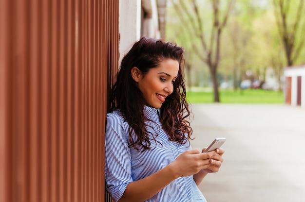 Ragazza carina in piedi accanto al muro e mandare sms
