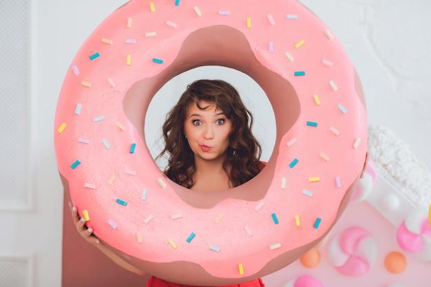 Ragazza carina in posa con ciambelle rosa, scherzare, dessert, cibo cattivo, guarda nel buco nella ciambella, mantiene le ciambelle dagli occhi