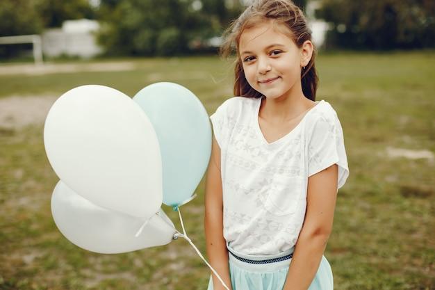 Ragazza carina in t-shirt bianca e gonna blu gioca nel parco estivo con palloncini