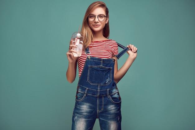 Ragazza carina in tuta di jeans e bicchieri con selz