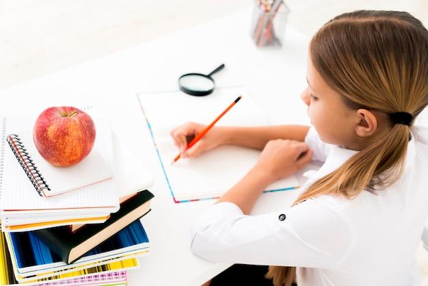 Ragazza carina in uniforme studiando alla scrivania