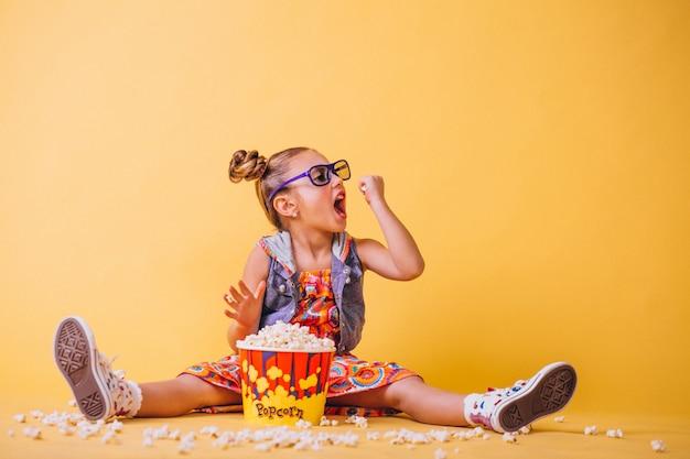 Ragazza carina mangiando popcorn