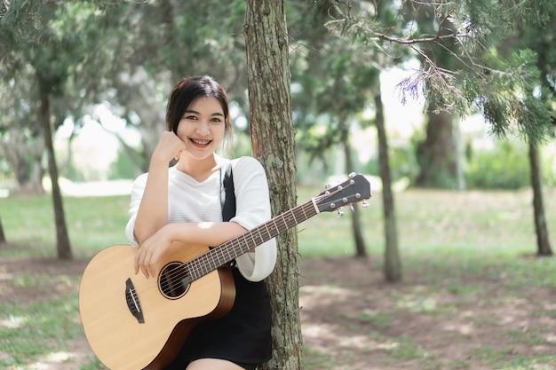 Ragazza carina ritratto suonare la chitarra in giardino