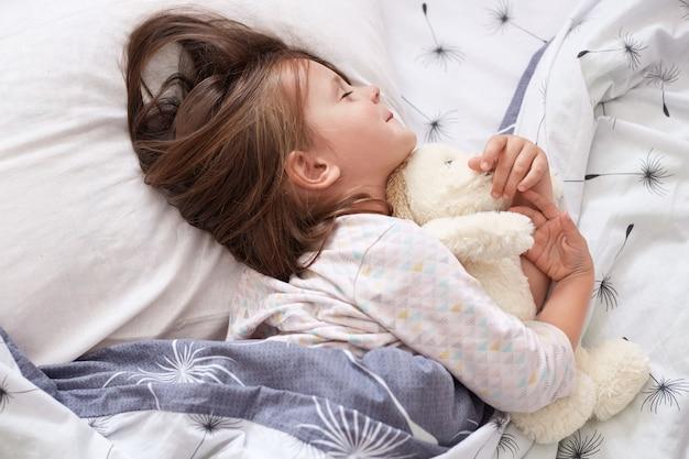 Ragazza carina sdraiata a letto, addormentarsi dopo un'intera giornata a giocare, sdraiata sul cuscino bianco sotto la coperta con gli occhi chiusi, affascinante bambino indossa il pigiama