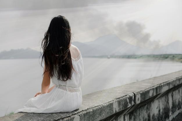Ragazza carina seduta con la schiena sul bordo della diga del serbatoio in solitaria e leggera fiera.