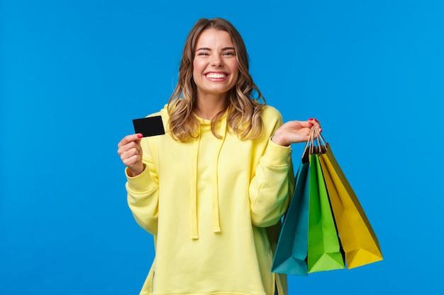 Ragazza carina sorridente felice usando la sua carta di credito, deposita denaro per lo shopping, tiene le borse con i vestiti e sorride felice, finalmente si prepara per le vacanze estive, su una parete blu