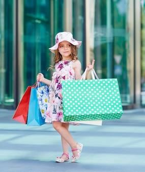 Ragazza carina su shopping, ritratto di un bambino con borse della spesa, shopping, ragazza.