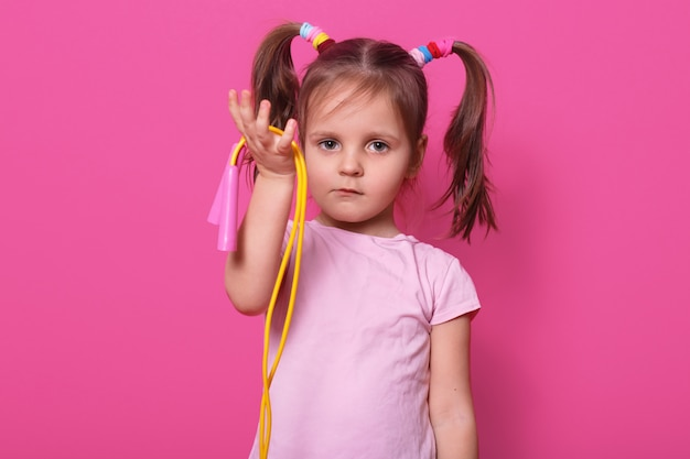 Ragazza carina, triste tiene in mano la corda per saltare. il piccolo bambino vuole giocare con qualcuno. adorabile bambino con code di cavallo e colorati scrunchies, indossa maglietta su rosa.