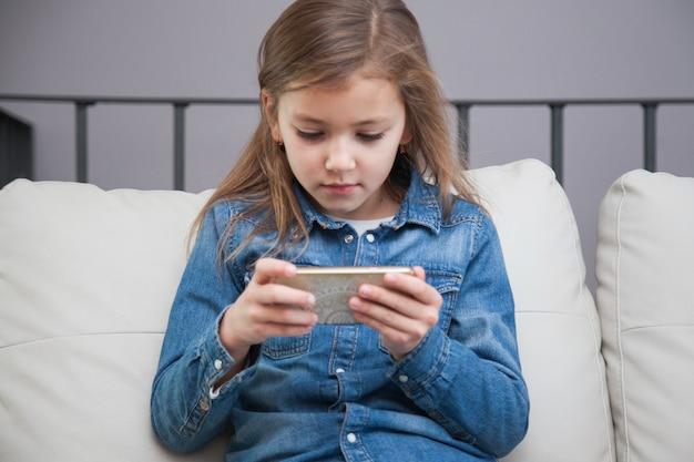 Ragazza carina utilizzando smartphone sul divano
