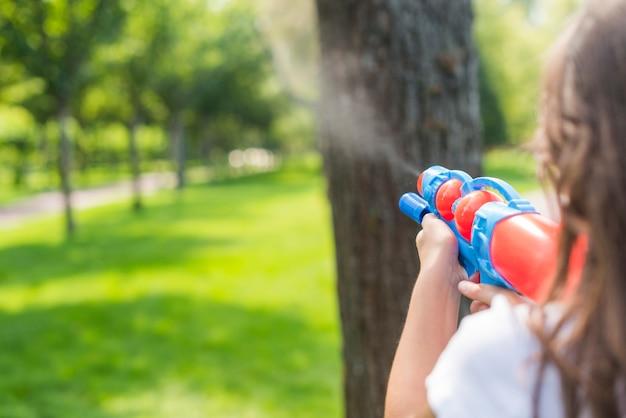 Ragazza carina vista posteriore giocando con una pistola ad acqua