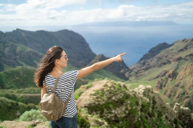 Ragazza castana abbastanza turistica che si rilassa vicino alle montagne.