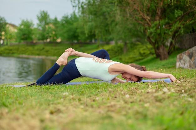 Ragazza castana caucasica snella che fa yoga di estate su un prato inglese verde dal fiume