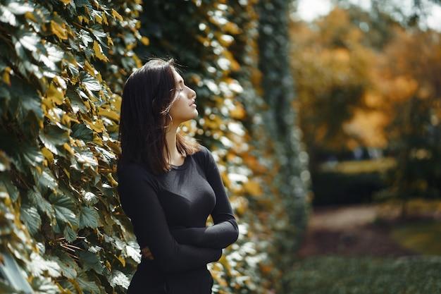 Ragazza castana che cammina attraverso il parco durante l'autunno