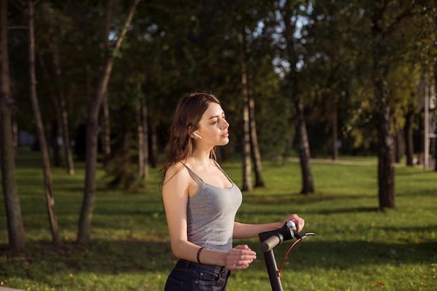 Ragazza castana che guida un motorino elettrico ecologico di scossa in un parco in tempo soleggiato sui marciapiedi