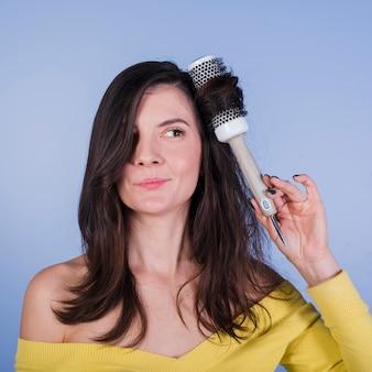 Ragazza castana che posa con la spazzola per capelli