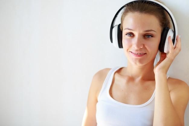 Ragazza castana con le cuffie che ascolta la musica mentre sedendosi sul pavimento