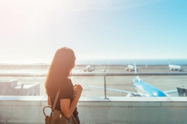 Ragazza castana dei capelli lunghi che aspetta partenza nell'aeroporto.