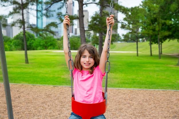 Ragazza castana del bambino che gioca con l'oscillazione sul parco della città