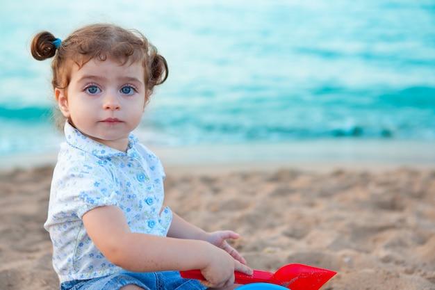 Ragazza castana del bambino degli occhi azzurri che gioca con la sabbia in spiaggia