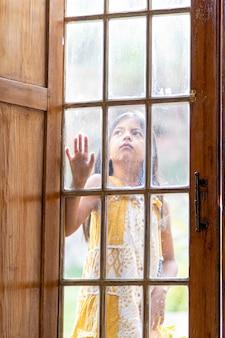 Ragazza castana dietro la porta di legno e di vetro