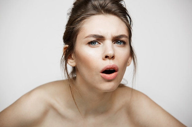 Ragazza castana dispiaciuta giovani con il fronte divertente che esamina macchina fotografica con la bocca aperta sopra fondo bianco.