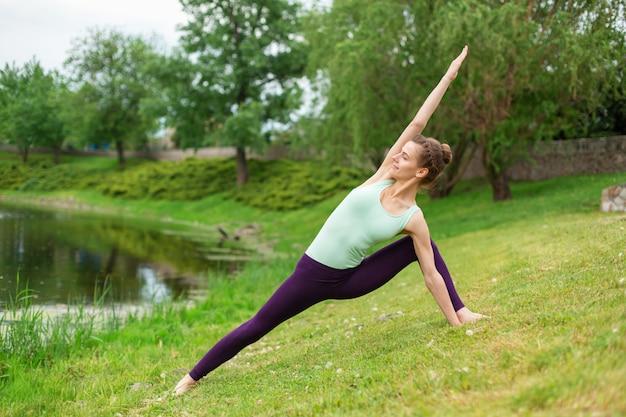 Ragazza castana esile che fa yoga di estate su un prato inglese verde sul lago