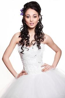 Ragazza castana felice felice della bella sposa in vestito da sposa bianco con l'acconciatura e trucco luminoso su fondo bianco
