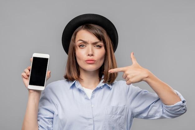 Ragazza castana in cappello e camicia che ti mostra la notifica nello smartphone mentre lo indica in isolamento